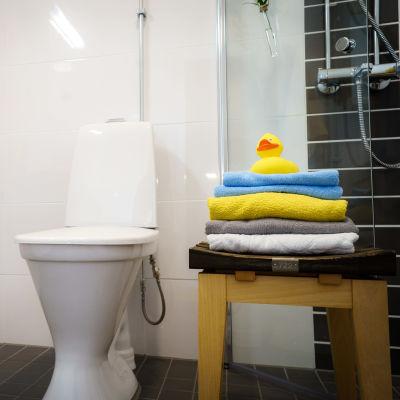 WC-pytty kylpyhuoneessa, vieressä pallilla pino pyyhkeitä.