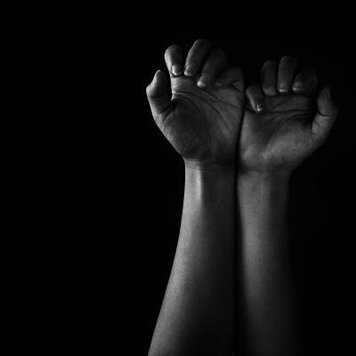 Knutna händer i mörker.