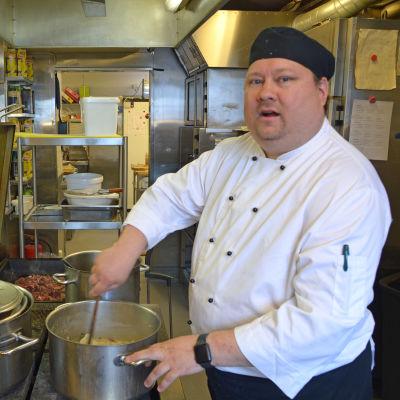 En manlig kock som lagar mat i köket.