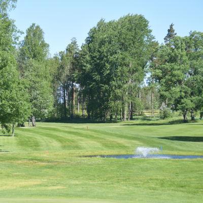 En golfbana med en liten fontän. Inga människor.