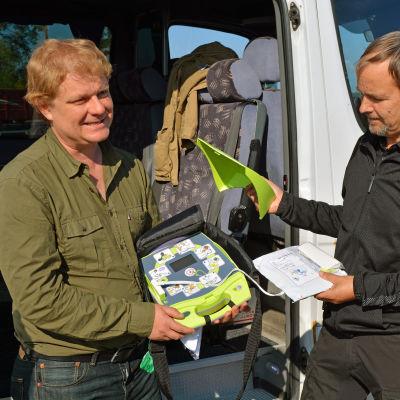 Mats Eriksson och Ari-Pekka Aarnio visar hur en hjärtstartare ser ut.