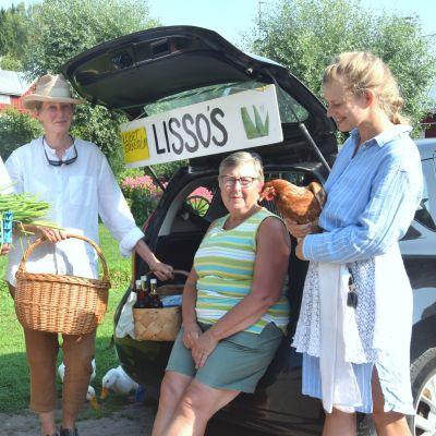 En man och tre kvinnor vid en bil en idyllisk sommardag. Mannen håller i en låda med lök, en av kvinnorna en korg och en annan har en höna i famnen. I bakgrunden en röd stuga.