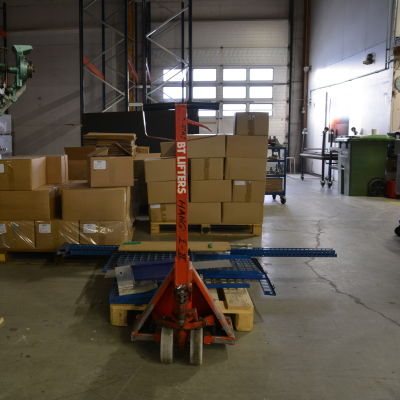 Maskin och papplådor i en hall.