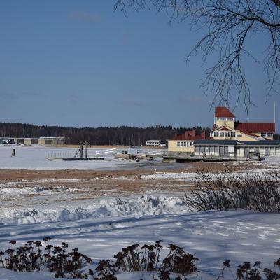 Sandstrand på vintern när det är snö och is. I bakgrunden en sommarrestaurang i trä.