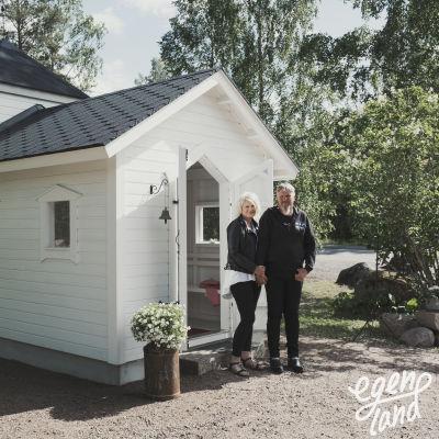 Nainen ja mies erittäin pienen, valkoiseksi maalatun puukirkon edustalla pitämässä toisiaan kädestä.