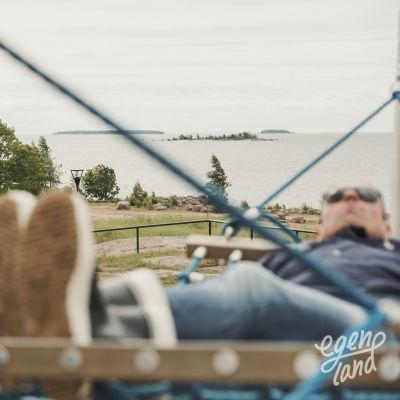 I förgrunden en man i gummistövlar som ligger i en hängmatta. I bakgrunden ett grönområde vid havet.