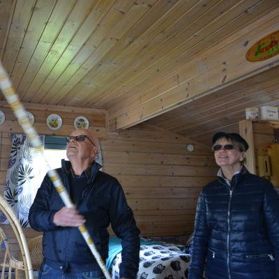 alf rehn bankar med en kvast i innertaket på stugan. bredvid står Karin westergård-hjerpe.