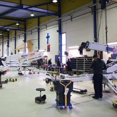Verkstaden på Dino Lifts fabrik i Loimaa. En person jobbar med en skylift, som produceras på fabriken.