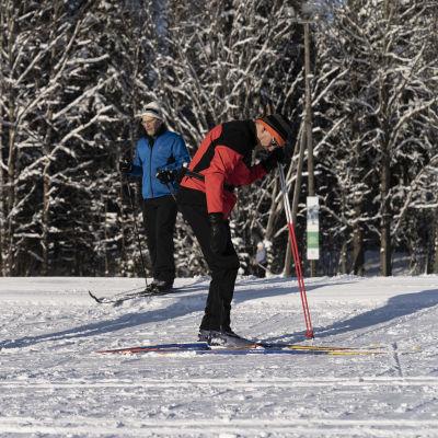 Mies laittaa suksia jalkaansa Paloheinän hiihtoladulla.