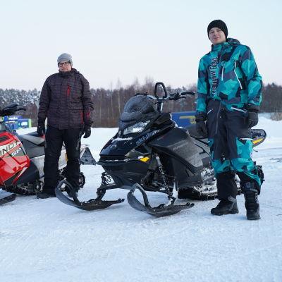 Mats Nyberg och John Björklöf står bredvid sina snöskotrar.