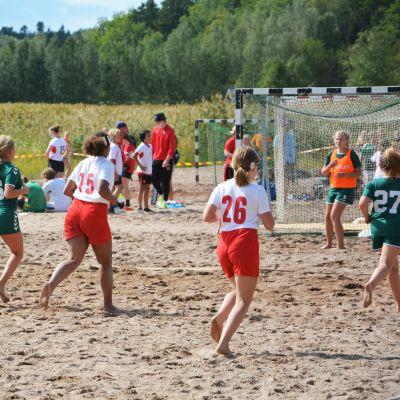Två handbollslag spelar handboll på en strand.