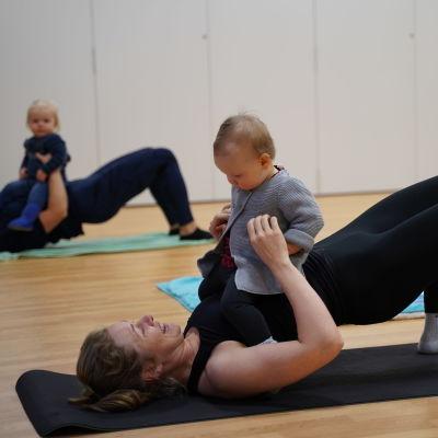 En kvinna ligger på rygg med en bebis i famnen.