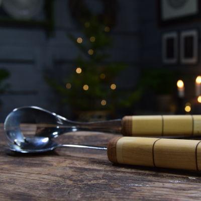 Salladsbestick med trädskaft i Strömsö villans sal på ett brunt bord