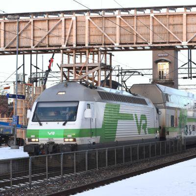 Tåg vid snöbeklädd perrong. I bakgrunden gångbro i trä.