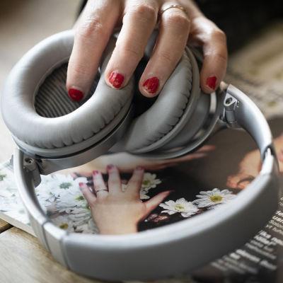En hand med rött slitet nagellack håller i ett par hörlurar som vilar på en tidning med en kvinna på omslaget.