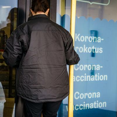 Henkilö menossa sisään koronarokotuspaikkaan. Ovessa lukee teksti koronarokotus.