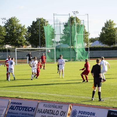Fotbollsmatch på gräsplan. Ena laget spelar i vita tröjor, det andra i röda.