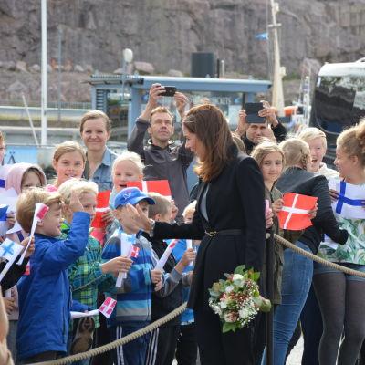 Kronprinsessan Mary hälsar på publiken och gör high-five med en pojke.