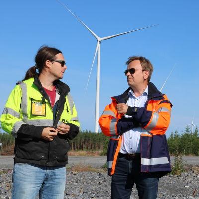 Tre män med skyddsjackor på står och diskuterar. I bakgrunden syns skog och vindkraftverk.