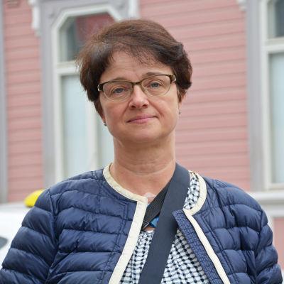 Kvinna står framför ett rosa stenhus.