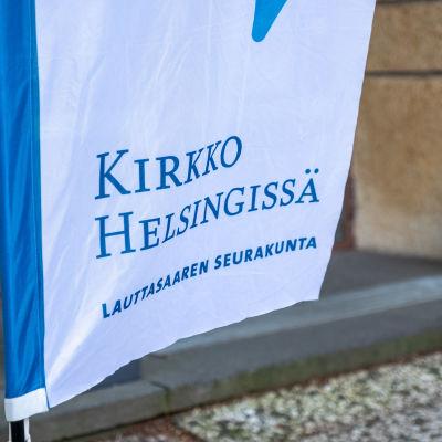 Lähikuva Kirkko Helsingissä -tekstistä Lauttasaaren seurakunnan sisäänkäynnin edustalla olevassa lipussa.