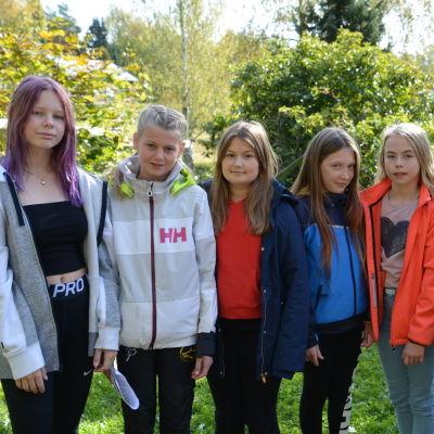 Sex glada 12-åringa flickor står bredvid varandra på en skolgård.