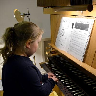 Flicka som spelar på orgel.