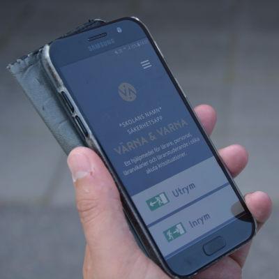 En hand som håller i en telefon.