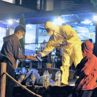 Suoja-asuun pukeutunut pelastustyöntekijä antaa desinfiointiainetta nuorella miehelle.