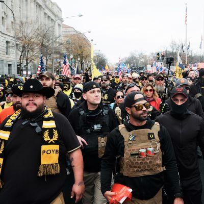 Suuri joukko Trumpin kannattajia marssii kadulla, Etualalla on pääosin mustiin pukeutunutta väkeä. Keskellä on Proud Boys -järjestön johtaja, parrakas Enrique Tarrio mustissa laseissa ja lippalakissa, jonka lippa on käännetty niskan puolelle.