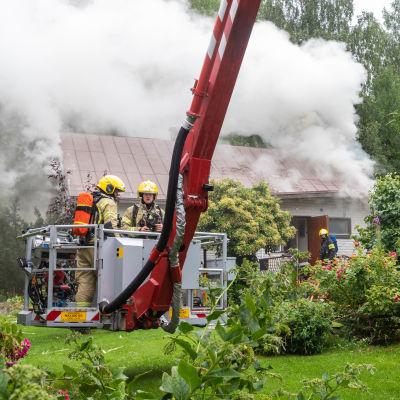 Brandmän i skylift släcker tak som brinner.