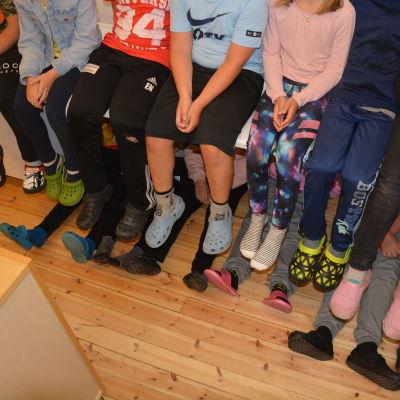 Skolelever har radat upp sig på och under en bänk så att man ser bara ben och fötter. De vill illustrera hur trångt de har det i skolan.