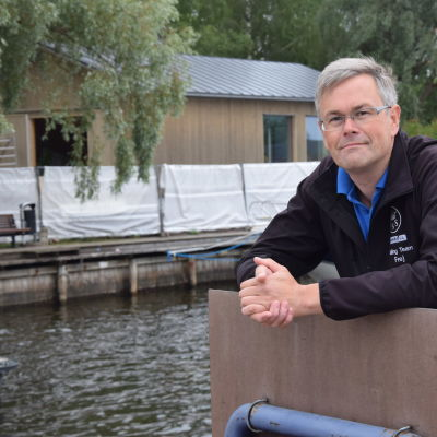 Vicekommodor Frej Werner poserar med Ekenäs Segelsällskaps nya klubbhus i bakgrunden.
