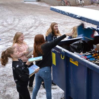 Flickor kastar böcker i en container.