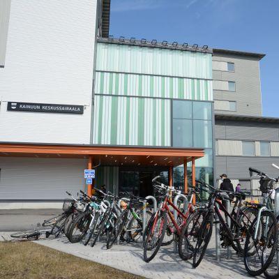 Kainuun uuden keskussairaalan pääsisäänkäynti kuvattuna keväällä. Etualalla rivi pysäköityjä polkupyöriä.