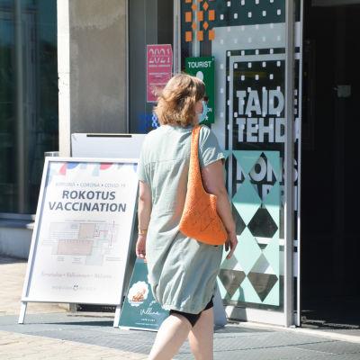 """Person i ljusgrön tunika med orange väska går mot ingången till Konstfabriken i borgå. Bredvid syns en skylt med texten """"Vaccination""""."""