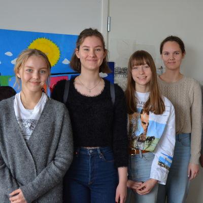 fem elever står vid en vägg