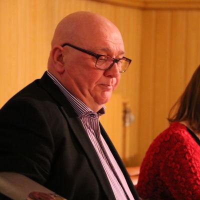 En medelålders man med glasögon sitter vid ett bord.