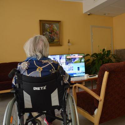 Tre invånare i ett äldreboende som ser på tv.