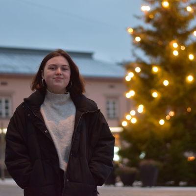 Emilie Jäntti, ordförande för Finlands Svenska Skolungdomsförbund, står på Ekenäs torg med en julgran i bakgrunden.