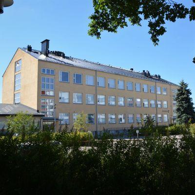 Gulaktig skolbyggnad i sten med texten Keskuskoulu.