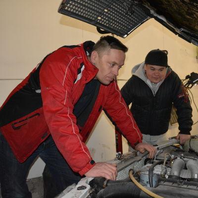Två män tittar på en bilmotor.