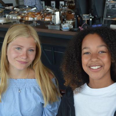 Två unga tjejer ler mot kameran.