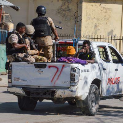 """Väpnade poliser på en bils öppna flak. Bilen är sliten och försedd med texten """"police""""."""