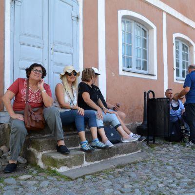 Ett gäng turister sitter på stentrappa framför Rådhuset.