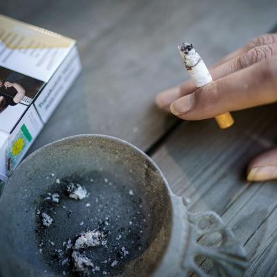 Naisen käsi pitelee savuketta pöydällä, jossa myös tuhkakuppi ja savukeaski.