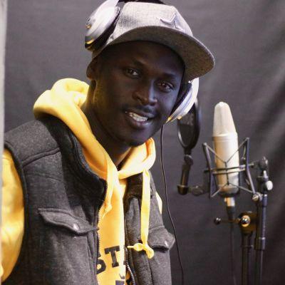 King Kaka i studion framför en mikrofon.