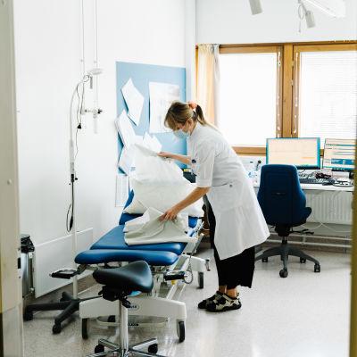 Sjukvårdare ordnar med skyddspapper på en mottagningsstol.
