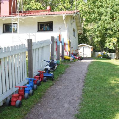 En bild på en gård där barntrampbilar står uppradade längsmed ett staket. På bilden syns hus och gräs