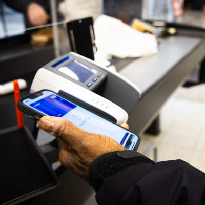 Henkilö maksaa mobiilisti ostokset ruokakaupassa.